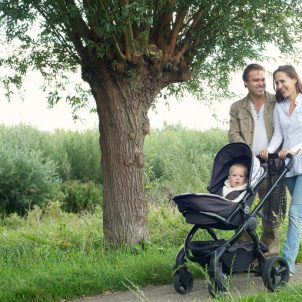 Portrait of a smiling young family walking outdoors and pushing baby in pram